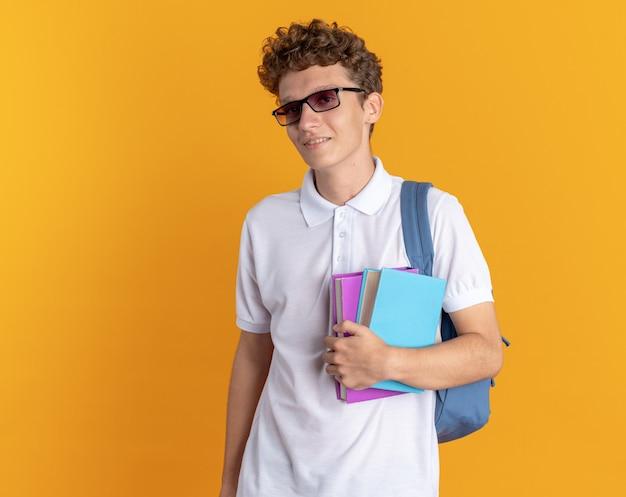 Student facet w swobodnym ubraniu w okularach z plecakiem, trzymający książki, patrzący w kamerę, uśmiechający się pewnie