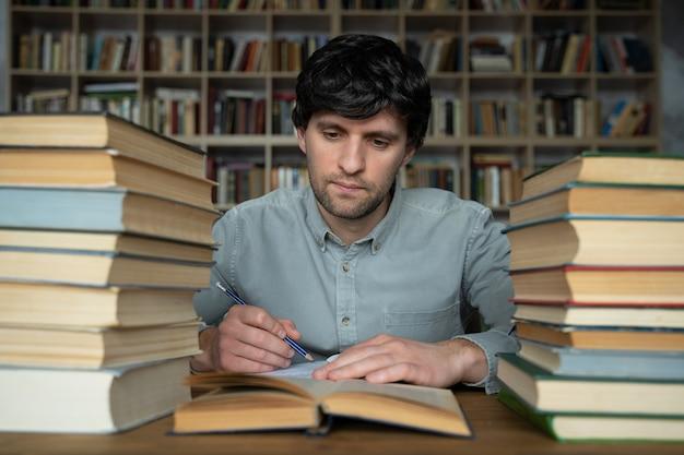 Student mężczyzna siedzi przy stole w bibliotece zaśmieconej książkami