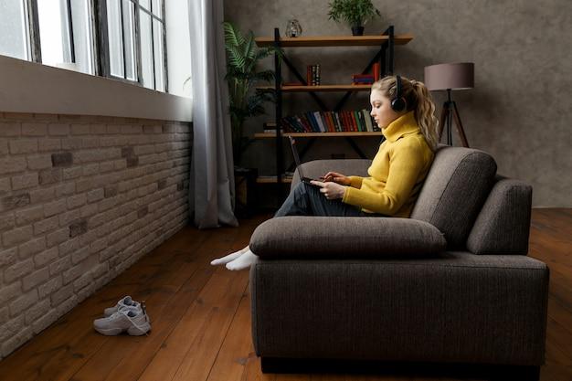 Student młoda dziewczyna studiuje w salonie, siedząc na kanapie i za pomocą słuchawek i laptopa.