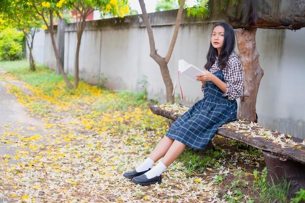 Student młoda dziewczyna trzyma książkę pod pięknym drzewem.