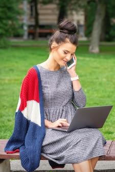 Student młoda kobieta rozmawia przez smartfona za pomocą laptopa na ławce w parku
