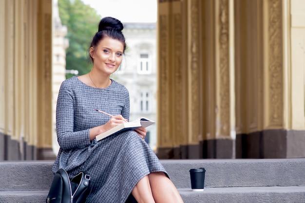 Student młoda kobieta z uniwersytetu czyta książkę na schodach.
