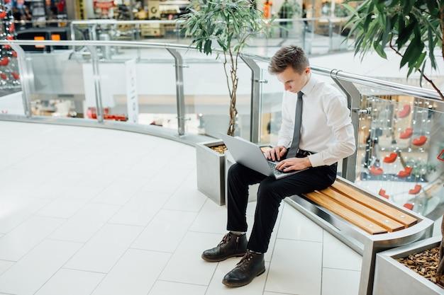 Student na poważnie pracuje przy komputerze, w centrum biznesowym, ubrany w białą koszulę,