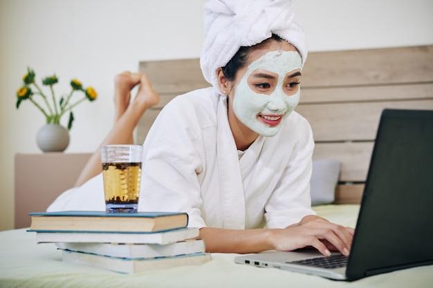 Student ogląda webinarium w łóżku