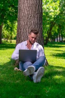 Student ogląda wideo na laptopie siedząc na trawie obok drzewa w wiejskim parku w słoneczny dzień