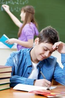 Student pisania i dotykając jego czoła