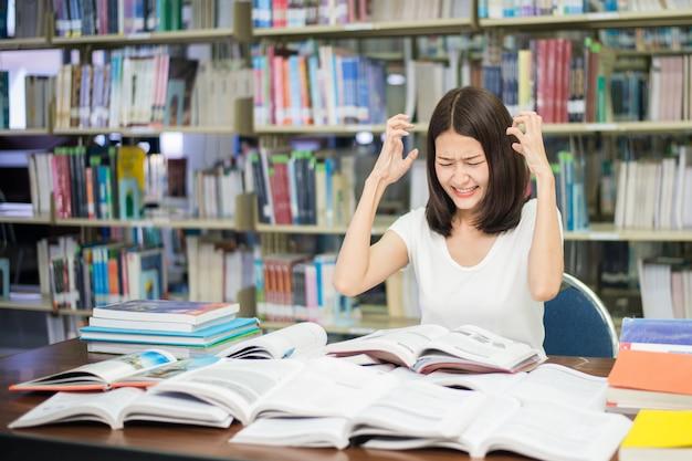 Student pod presją psychiczną podczas czytania książki przygotowanie egzaminu w bibliotece na uniwersytecie.