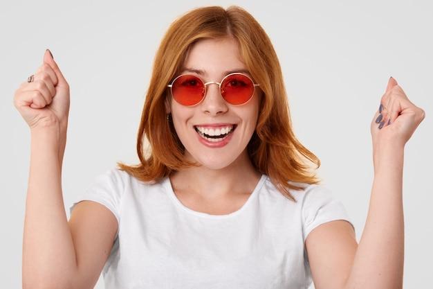Student podnosi pięści z triumfem i szczęściem, cieszy się z udanego egzaminu, nosi czerwone okulary przeciwsłoneczne