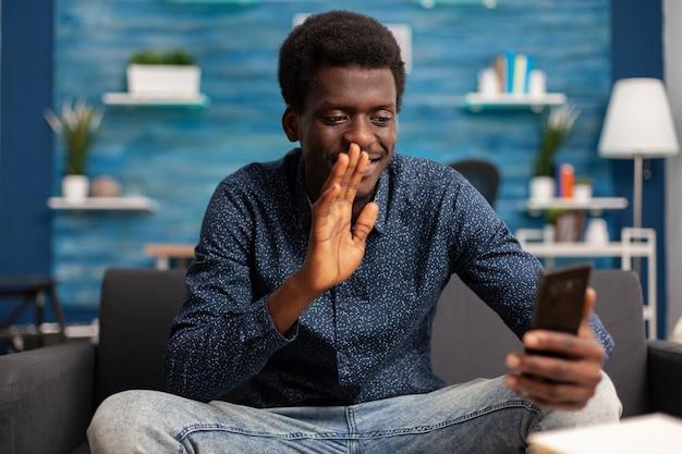 Student pozdrawiający zdalnego kolegę omawiającego pomysły biznesowe na kurs uniwersytecki podczas telekonferencji online przy użyciu smartfona w salonie. telepraca konferencyjna