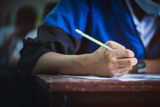 Student przystępujący do egzaminu podczas noszenia maski na twarz z powodu zagrożenia związanego z koronawirusem. młoda kobieta siedzi w klasie z maską chirurgiczną z powodu pandemii covid-19