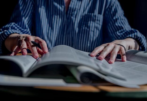 Student ręce zbliżenie trzymając długopis i czytając wiele książek koncepcja badań i szukanie odpowiedzi...