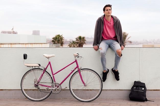 Student siedzący zamyślony ze swoim zabytkowym rowerem i plecakiem z koncepcją zrównoważonego transportu