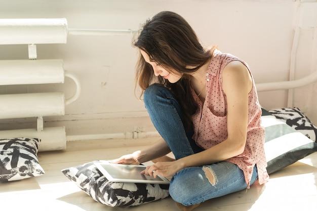Student siedzi na podłodze i używa laptopa lub surfuje po sieci