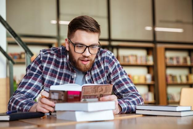 Student siedzi przy biurku i czyta książkę w bibliotece