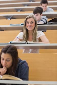 Student siedzi w sali wykładowej, jednocześnie uśmiechając się