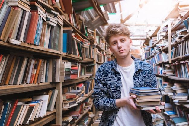 Student stoi w klimatycznej bibliotece z książkami w rękach i patrzy w kamerę.