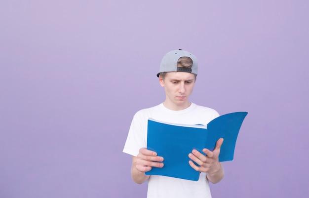 Student stoi z czasopismem na tle fioletowej ściany i czyta