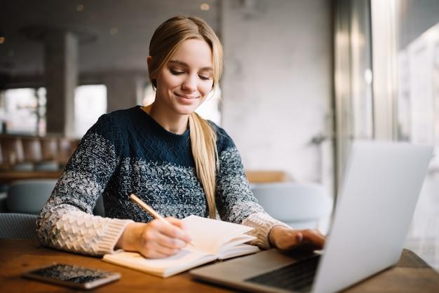 Student studiujący, korzystający z laptopa, edukacja online. piękna kobieta freelancer pisze notatki, planuje projekt pracy, pracuje z domu