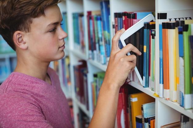 Student trzyma cyfrowy tablet na półce w bibliotece