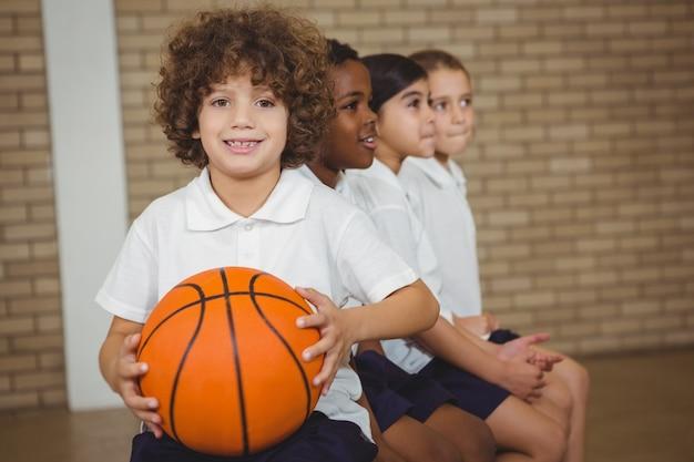 Student trzyma koszykówkę z innymi graczami