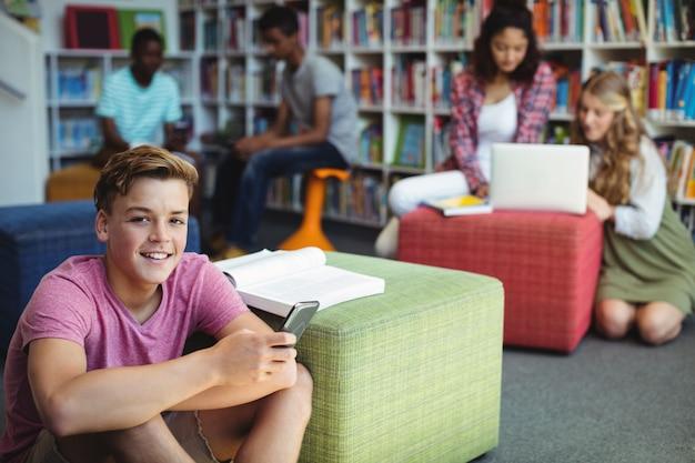 Student trzyma telefon komórkowy w bibliotece