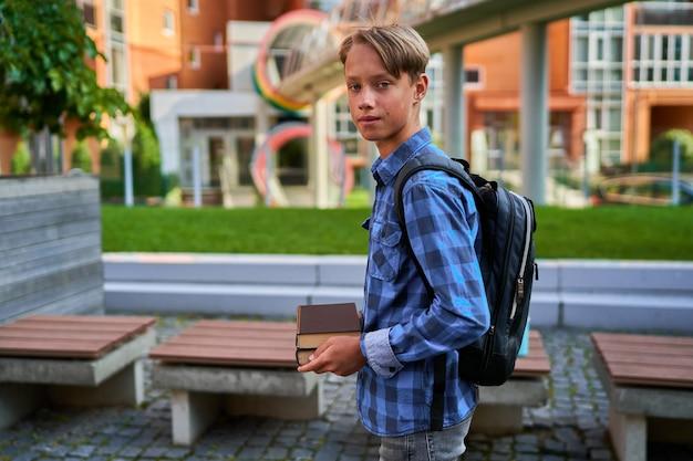 Student trzyma w rękach wiele książek.