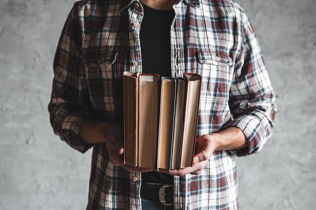 Student trzymając w ręku stos starych książek. nauka, sukces, wiedza