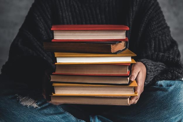 Student trzymając w ręku stos starych książek.