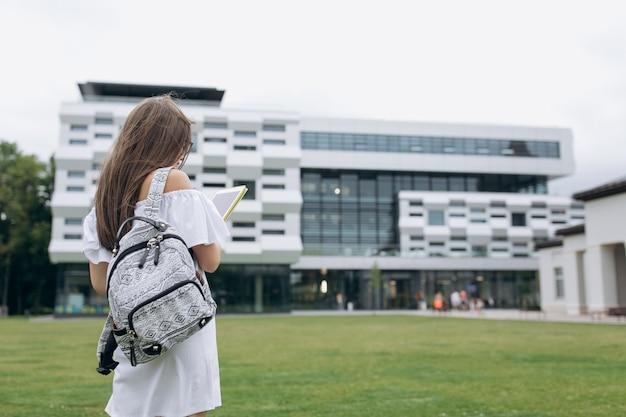 Student uniwersytetu na zewnątrz na terenie kampusu. student z plecakiem. młody szczęśliwy uczeń. studenci chodzący na zewnątrz po kampusie uniwersyteckim