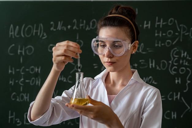 Student w białym fartuchu i okularach trzyma w rękach kolbę i przeprowadza eksperyment, koncepcja edukacji uniwersyteckiej