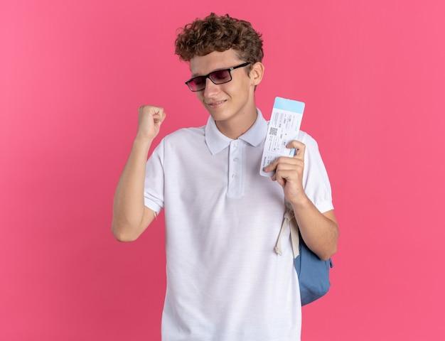 Student w luźnym ubraniu, w okularach i plecaku, trzymający bilety lotnicze