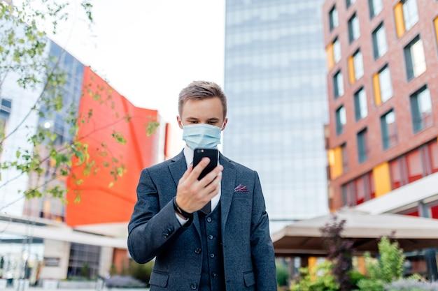 Student w oficjalnym garniturze i masce medycznej do zapobiegania koronawirusowi, rozmawiający na smartfonie, stojąc w centrum miasta