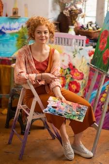 Student w trampkach. stylowy młody rudowłosy student sztuki w trampkach trzymając paletę kolorów
