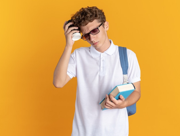 Student w ubraniu na co dzień w okularach z plecakiem trzymającym książkę i papierowy kubek wyglądający na zmęczonego