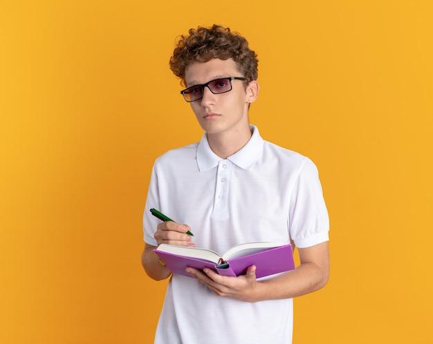 Student w ubraniu w okularach, trzymający książkę i ołówek, patrzący na kamerę