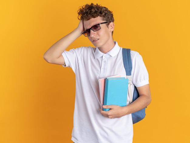Student w ubraniu, w okularach, z plecakiem i książkami, wyglądający na zdezorientowanego