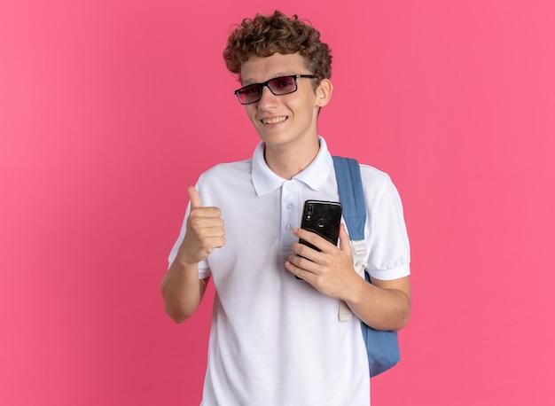 Student w ubraniu, w okularach, z plecakiem, trzymający smartfona
