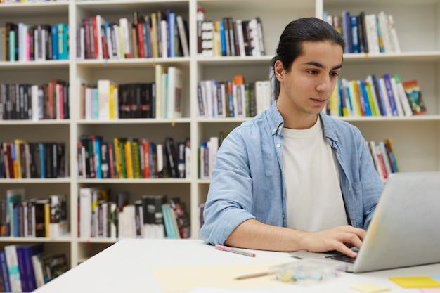 Student z ameryki łacińskiej za pomocą laptopa w bibliotece