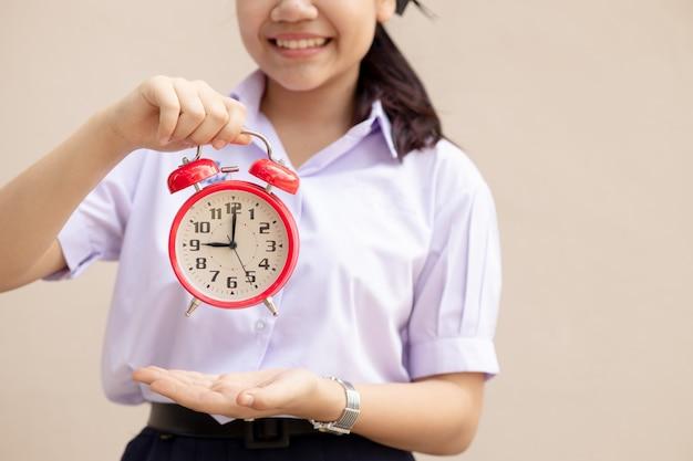 Student z azji obsługuje budzik na czas edukacji lub idzie do szkoły z radosnym uśmiechem.