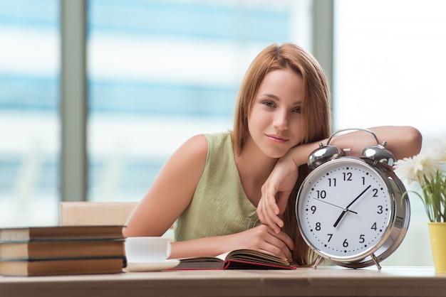 Student z budzikiem gian przygotowuje się do egzaminów