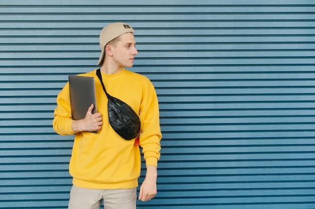 Student z laptopem w ręku i saszetką na szyi na stojąco