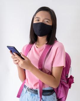 Student z maską na twarzy i smartfonem nosi różową koszulę