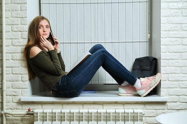 Student z smartphone, młoda piękna kobieta z plecakiem zeszyty siedzi