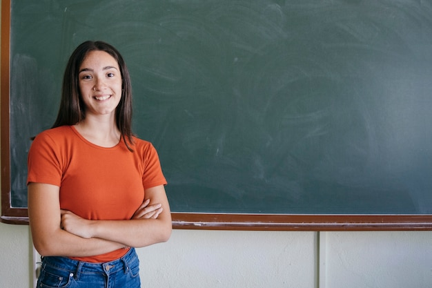 Student z tablica uśmiecha się i przekraczanie jej ramiona