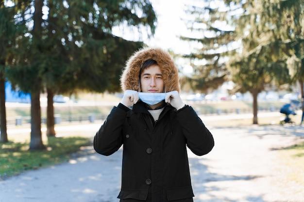 Student zakłada sterylną maskę medyczną chroniącą twarz przed koronawirusem covid 19