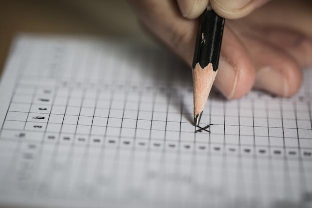 Student zdaje egzaminy, egzamin pisemny na papierowym arkuszu odpowiedzi forma optyczna znormalizowanego testu na biurku