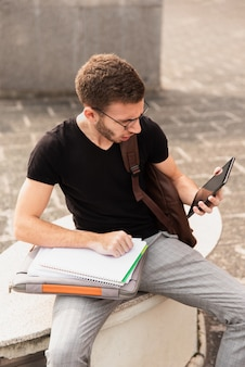 Studenta uniwersytetu obsiadanie na ławce i patrzeć pastylkę