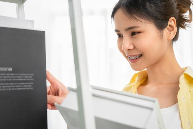 Studentka azjatka trzyma książkę w ręku i wybiera traktat z półki do przeczytania.