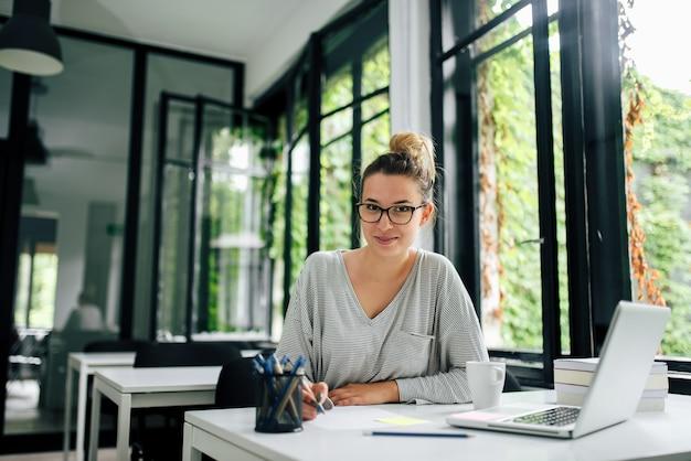 Studentka college'u studiująca w bibliotece uniwersyteckiej lub gabinecie. patrząc na aparat.