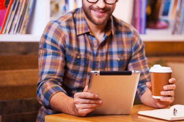 Studentka epoki cyfrowej. zbliżenie wesoły młody człowiek trzymający filiżankę kawy i patrzący na swój cyfrowy tablet siedząc przy biurku z półką na książki w tle